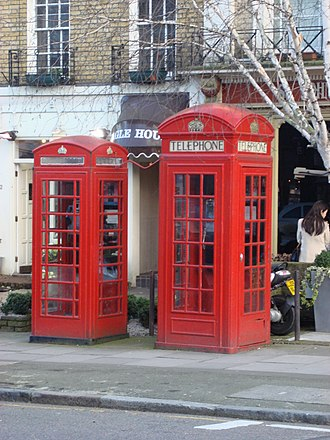 Street furniture - K2 and K6 (left) Red telephone boxes stand next to each other on St John's Wood High Street, London, England.