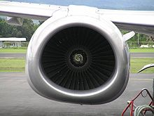 A zoomed-in view of the front of an engine nacelle. The fan blades of the engine are in the middle of the image. They are surrounded by the engine nacelle, which is seemingly circular on the top half, and flattened on the bottom half.