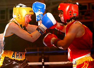Cutman - PFC Raelina Shinn (left) battles on with a nosebleed during the first female fight in the Armed Forces Boxing Championships.