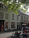 foto van Huis met eenvoudige witgeschilderde lijstgevel en dwars zadeldak