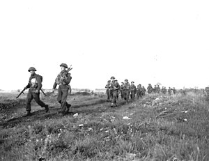 7th Canadian Infantry Brigade - Men of the Royal Winnipeg Rifles on the march in Normandy, July 1944.