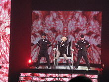 A blond female singing on stage. She wears a black top and long boots on her legs and holds a microphone to her mouth with her left hand. Four male performers in black hats and tail coats flank her. The backdrop display a long array of pink candy in circular motion.
