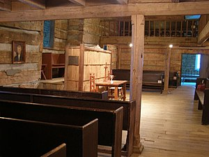 Photograph of the interior of an old log church with a rough hewn timber supporting column near the center of the image. The column supports a timber beam. Other beams are visible supporting a balcony that surrounds the room on three sides, the photograph is facing towards a communion table at the front of the church, and is taken from the left side of the room beneath the balcony. Plane wooden pews are visible to the left and on the other side of the room, the floor is wooden. A portrait of Thomas Campbell is visible to the left, on the front wall of the room.