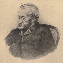 Black-and-white depiction from the waist up of an old, bearded man dressed in a dark jacket, sat in a chair and looking towards the left.