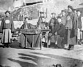 Chinese officials gathered around a table hearing cases and collecting taxes in a Chinese village, ca 1898-1904 (CHANDLESS 169).jpeg
