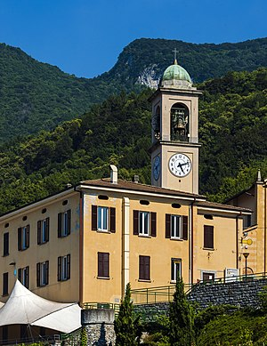 Two yellow two-story buildings, one with a clock tower reading 5:12, seen from a low angle. Behind them is a forested mountain and blue sky.
