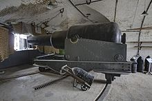View of the interior of a casemate, which is nearly filled with the bulk of a replica 12.5-inch gun