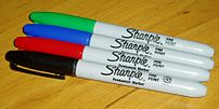 Four Sharpier permanent markers, showing black...