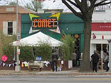 "A green storefront with a large orange and yellow logo that reads ""Comet"" in all capital letters."