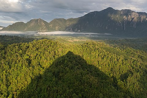 Conical shadow of Mount Nam Xay over green trees at golden hour, South-West view from the top, Vang Vieng, Laos