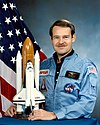 man in flight suit holding Space Shuttle mode, American flag in background