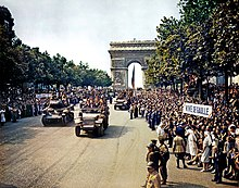 "Crowds line the Champs Elysees as tanks and half tracks roll down it. The Arc de Triomphe is in the background. People are holding a sign that reads: ""Viva de Gaulle""."