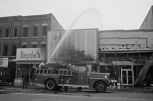 1968 Washington, D.C. riots - A firetruck douses smoldering shops burnt out during the riots