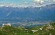La città con i primi contrafforti delle Dolomiti, ripresa dal Col Visentin sulla dorsale prealpina.
