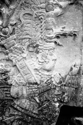 Relief sculpture of an elaborately dressed figure facing right, wearing an intricate headdress and cradling a staff in one arm.
