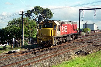 """New Zealand DX class locomotive - DX 5356 leaving Avondale in the late 1980s. The locomotive is painted in the International Orange or """"Fruit Salad"""" livery of NZR from the late 1970s onwards. Note the single front window above the short hood."""
