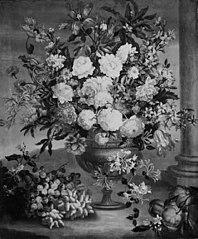 Stor blomsterbuket i en vase. I forgrunden frugter