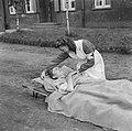 Een ziek op een brancard met een verpleegster, Bestanddeelnr 900-5044.jpg