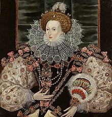 A three-quarter portrait of a middle-aged woman wearing a tiara, bodice, puffed-out sleeves, and a lace ruff. The outfit is heavily decorated with patterns and jewels. Her face is pale, her hair light brown. The backdrop is mostly black.