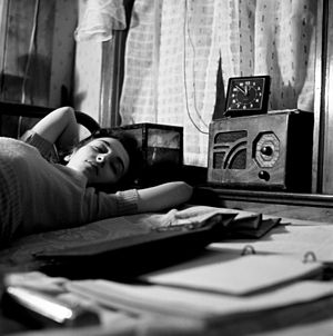 Photo of a female lying on a bed, listening to...