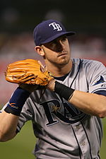 "A man in a gray and blue baseball uniform with the letters ""TB"" on his cap holds a baseball in his glove, preparing to throw."