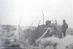 Mercenarios deJulio Poppersaqueando una tienda selknam, mientras otros disparan a mansalva contra los que huyen.