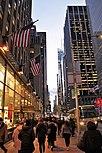 Des gratte-ciel bordent un trottoir très fréquenté le long de la 6e Avenue à New York City