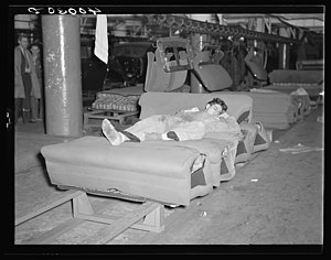 Flint sit-down strike - Young striker off sentry duty sleeping on assembly line of auto seats