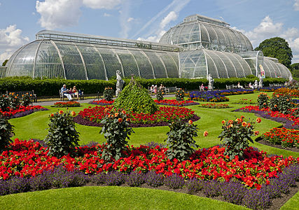 A front view of the Palm House at Kew Gardens showing the flowers planted in front