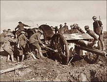 a collection of men pulling a field gun through the mud
