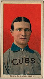 "A man with brown hair wearing a grey baseball uniform with a blue collar and the word ""CUBS"" on his chest in front of a red background"