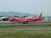 Fuji Dream Airlines Embraer 170 in red livery taking off at Kumamoto Airport