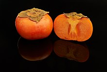 round, orange-coloured fruits, one whole and one cut in half