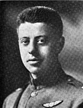 Head and shoulders of man in uniform. He has no tie; the tunic is buttoned at the neck. He wears a pair of wings on the breast and a Sam Brown belt.