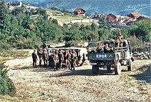 Three trucks of soldiers idle on a country road in front of trees and red-roofed houses. The rear truck has KFOR painted on is back.