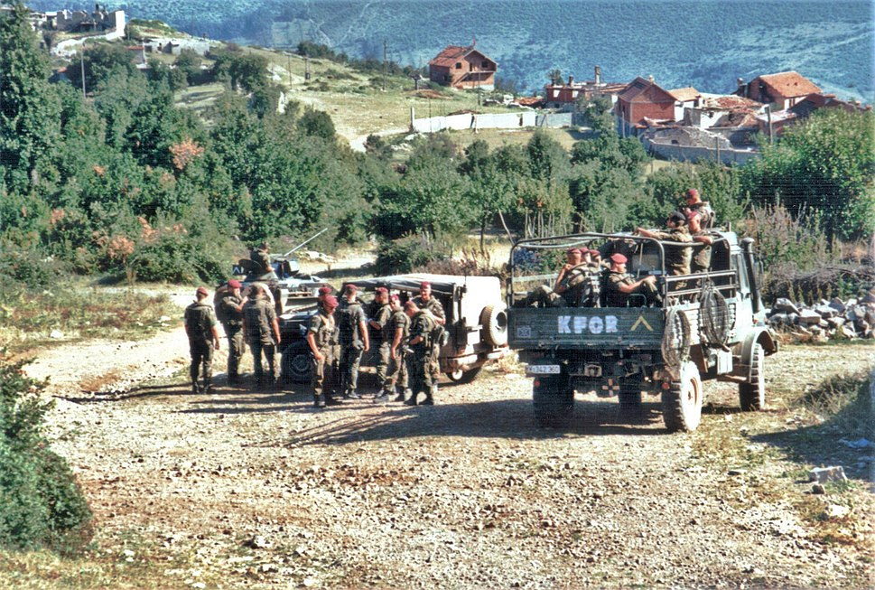 Three trucks of soldiers idle on a country road in front of trees and red roofed houses. The rear truck has KFOR painted on is back.