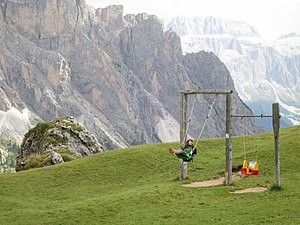 Swing (seat) - Girl on a swing in the Dolomites