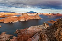 Aerial view of talls red rock mesas risign above the reservoir with a cloudy sky