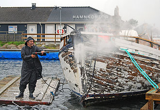 Pressure washing - A pressure washer is used to remove old paint from a boat.
