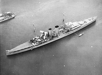 HMS Exeter (68) - Oblique aerial view of Exeter at anchor with awnings rigged, Balboa, Panama, 24 April 1934