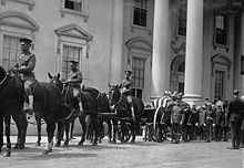 A black-and-white photograph of a procession of people in uniforms, some of whom are riding horses, all standing in front of a white building