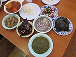 Clockwise from bottom: squid luau, pipikaula shortribs, kalua pig, tripe stew, rice, opihi poke, laulau, and poi in the center