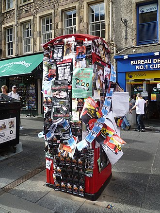 Edinburgh Festival Fringe - Fringe show flyers and posters compete for space on a High Street phone booth