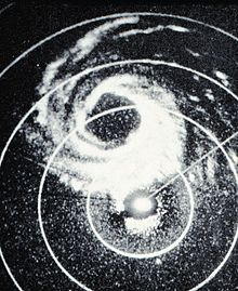 Monochrome radar image of a hurricane. Rain, which the radar detects, is shown as white regions. Concentric circles denote distances from the radar site, located slightly offset from the center of the image.
