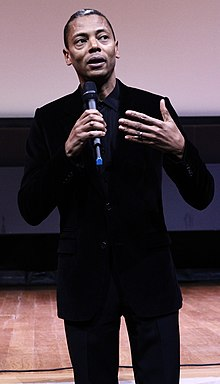 A man holding a microphone and giving a speech