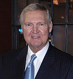 A head shot of an older man wearing a black suit and blue tie.