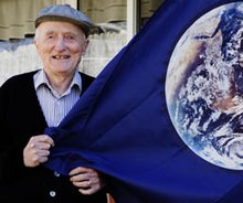Elderly man in a collared shirt and hat standing, holding a blue flag with a picture of planet Earth on it