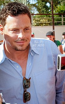 Justin Chambers in a blue shirt looking away from the camera
