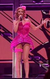 Una fotografía de Minogue vestido con un traje rosa cantando en un escenario