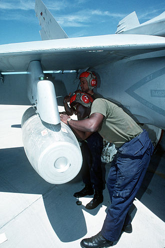 Mark 77 bomb - A Mark 77 bomb being loaded on an F/A-18 Hornet, 1993.